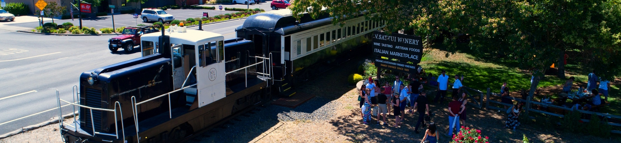 Napa Valley Wine Train stopped at a winery in the summer as a group of people prepare to board