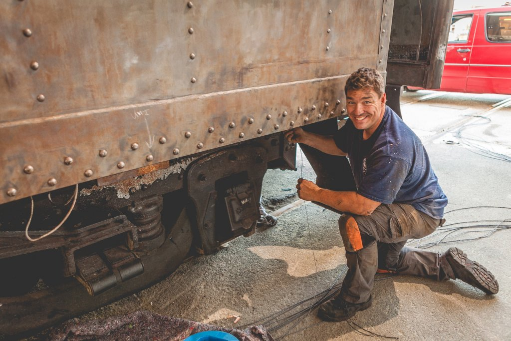A restoration worker kneels outside an antique railcar that is being refurbished.