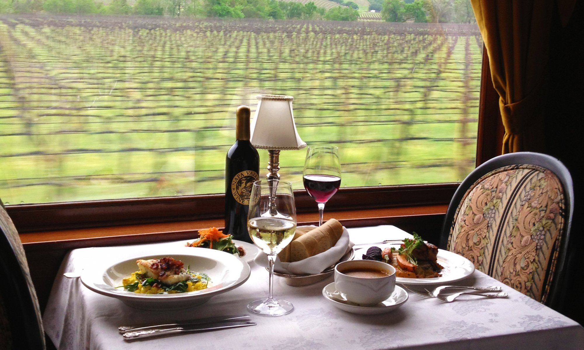 A dining table with two glasses of wine and 2 meals aboard the Napa Valley Wine Train