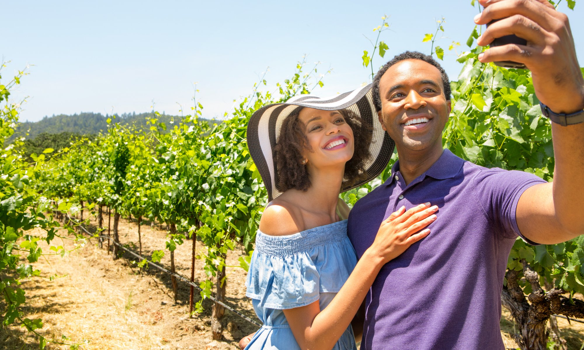 A couple take a selfie in a sunny, Napa Valley vineyard.