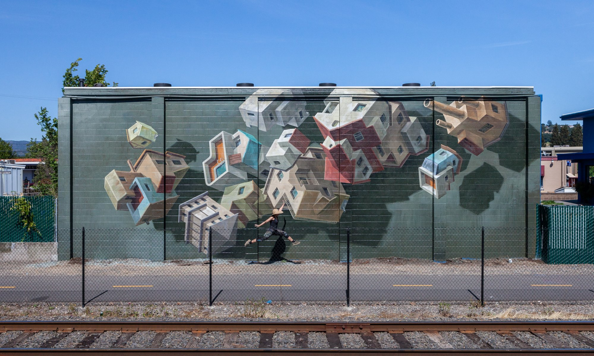 A woman leaps in front of a modern mural.