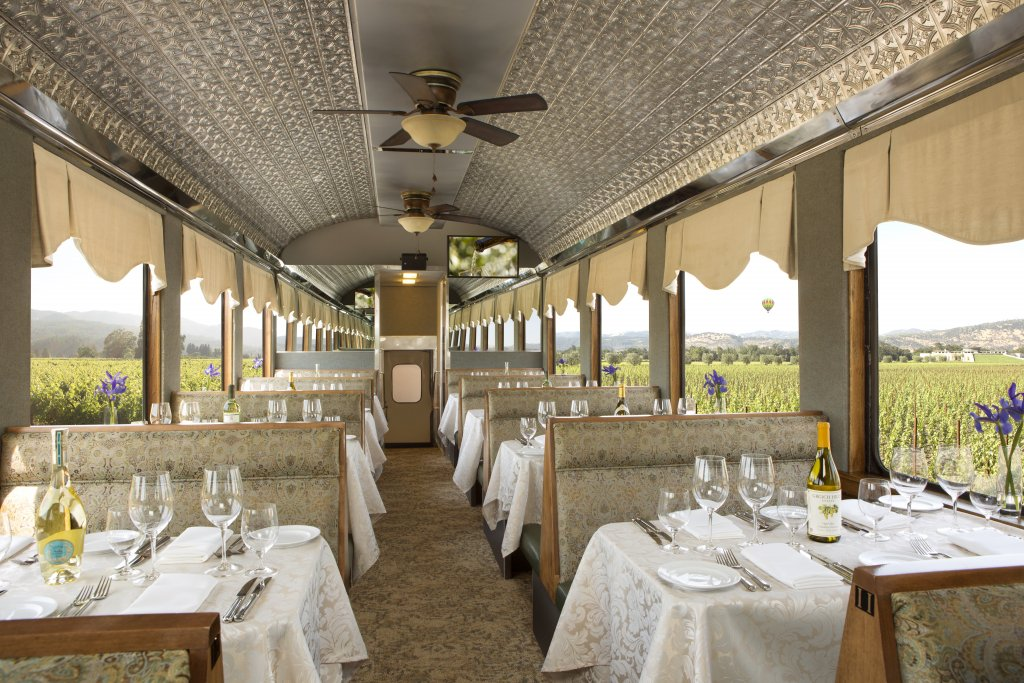 The interior of a renovated vintage open-air railcar, with tables set for a gourmet meal.