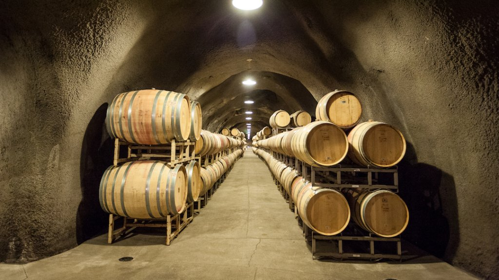 Wine barrels line an underground tunnel.