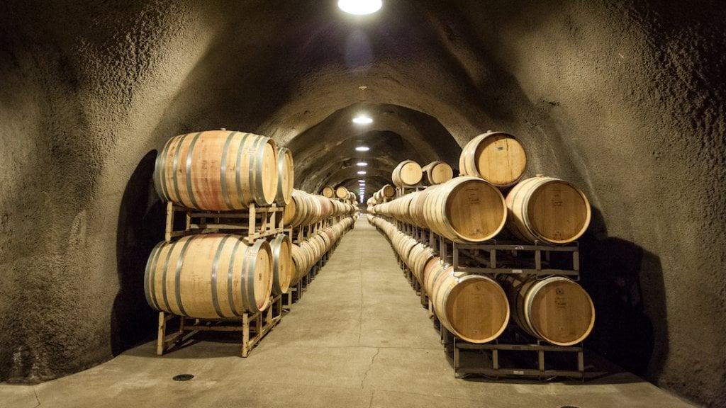 Wine barrels line an underground tunnel.