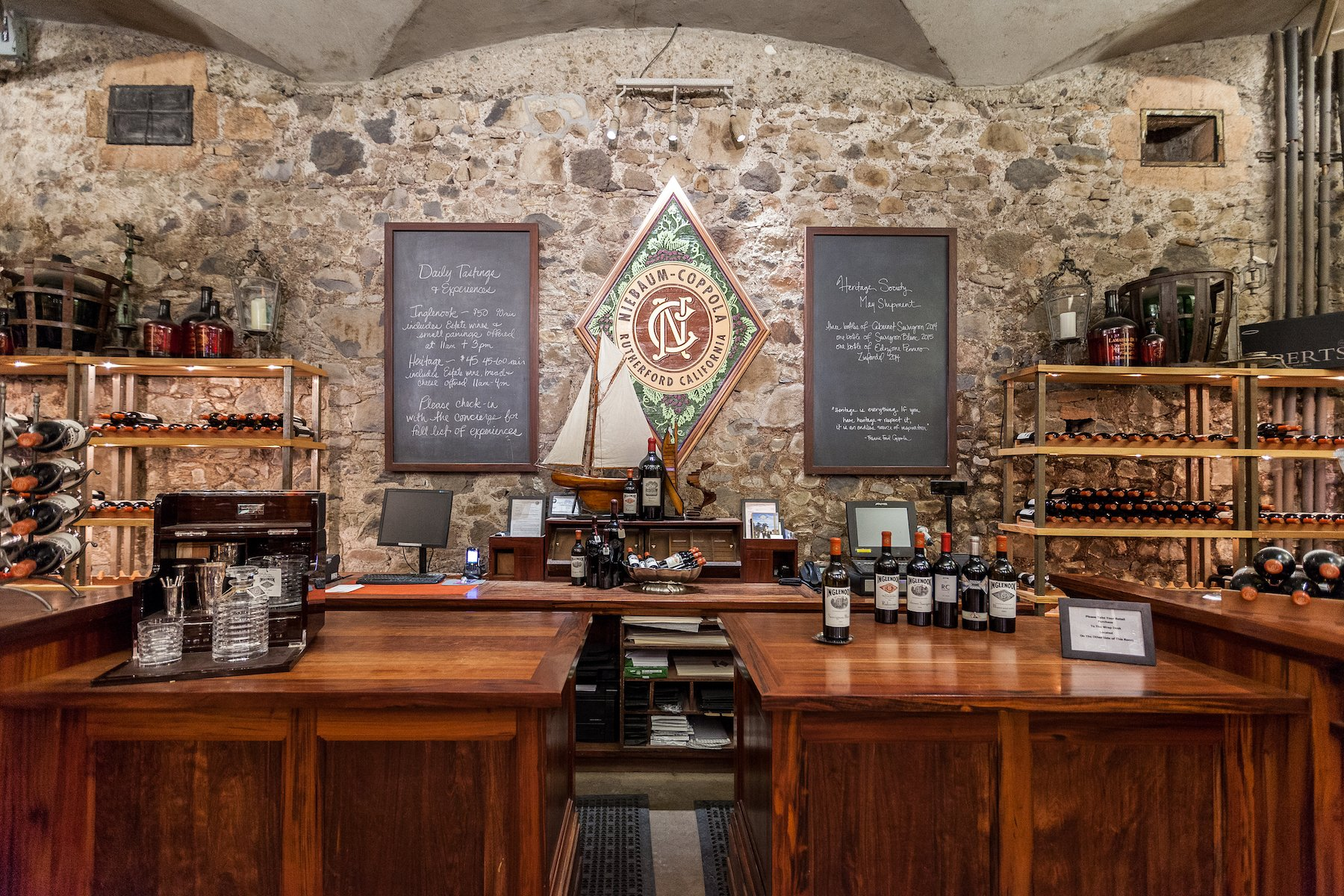 A wooden bar with bottles of wine on shelves at Inglenook winery in Napa Valley