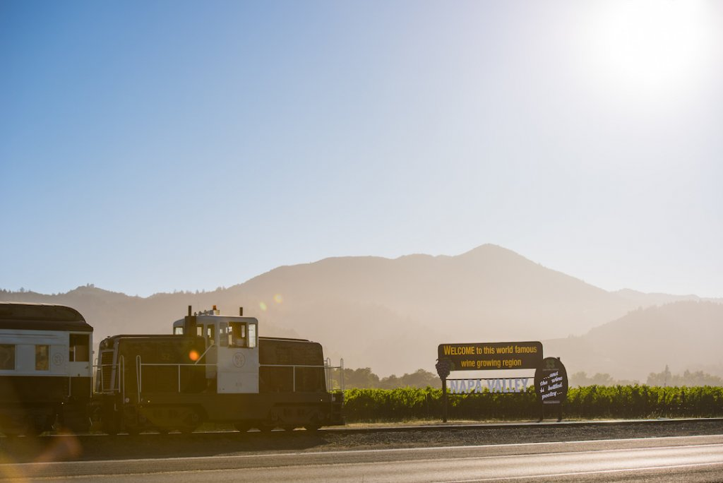 The Napa Valley Wine Train passes by a Welcome to Napa Valley sign.