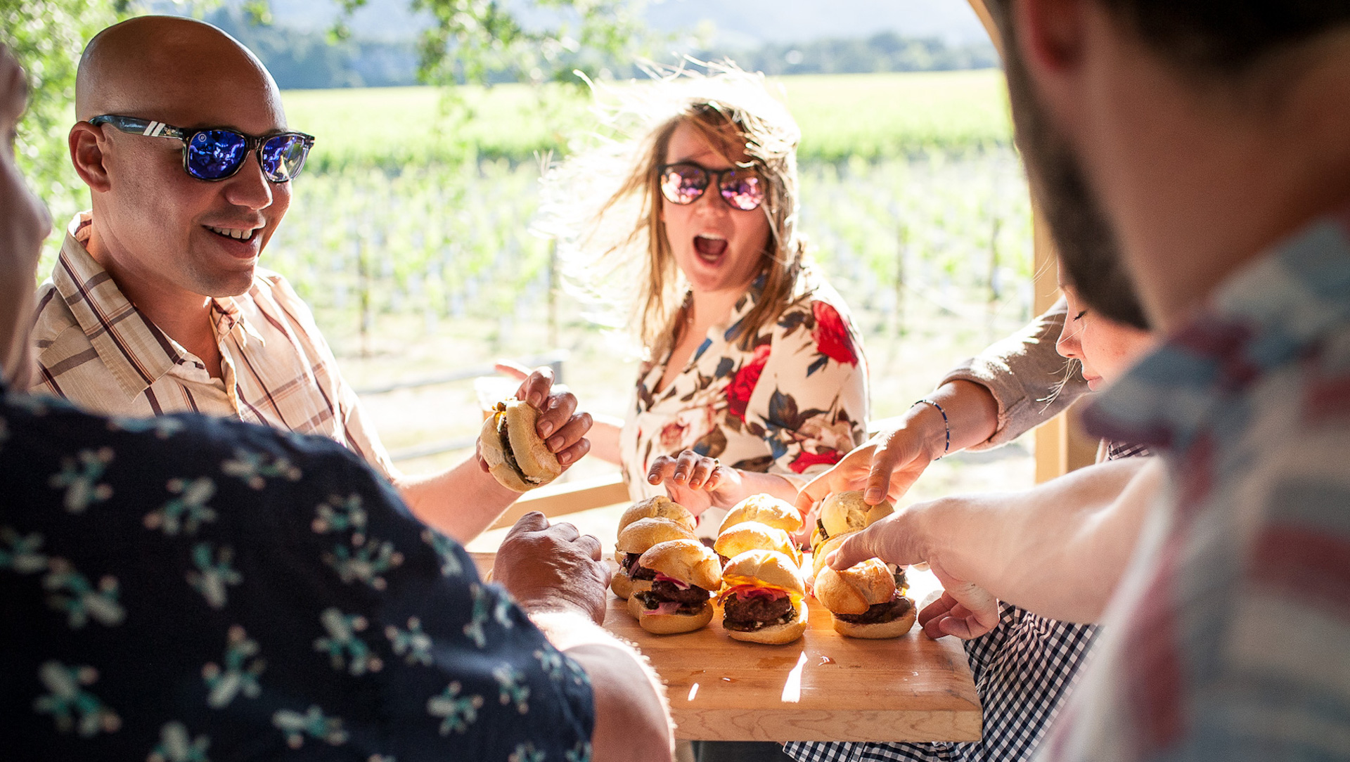 Group of grabbing burgers off of wooden tray at vineyard in Napa Valley