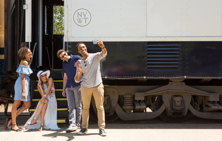 A group of 4 people take a selfie on cell phone before boarding the Napa Valley Wine Train