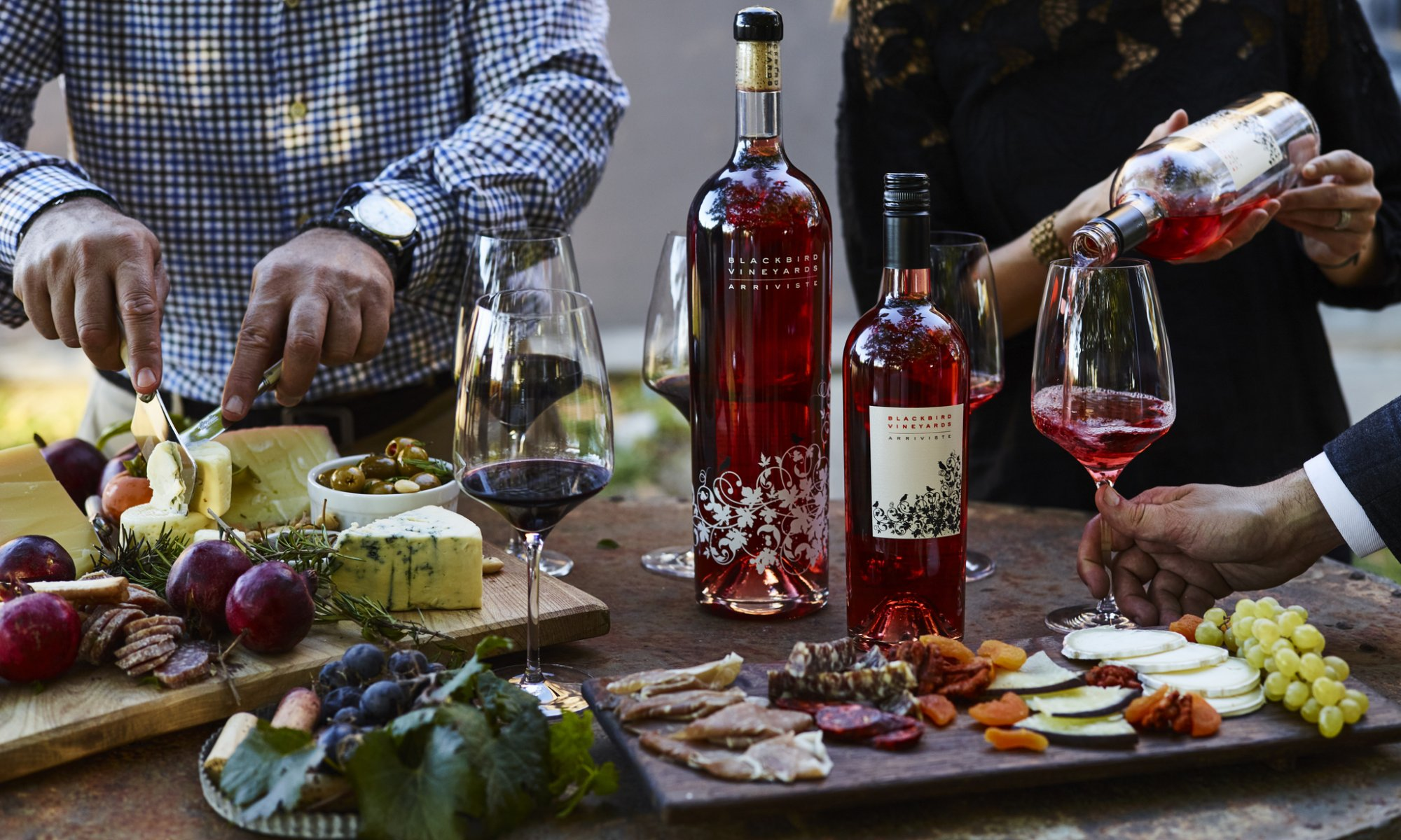 Bottles of wine, glasses of wine and charcuterie boards on a table