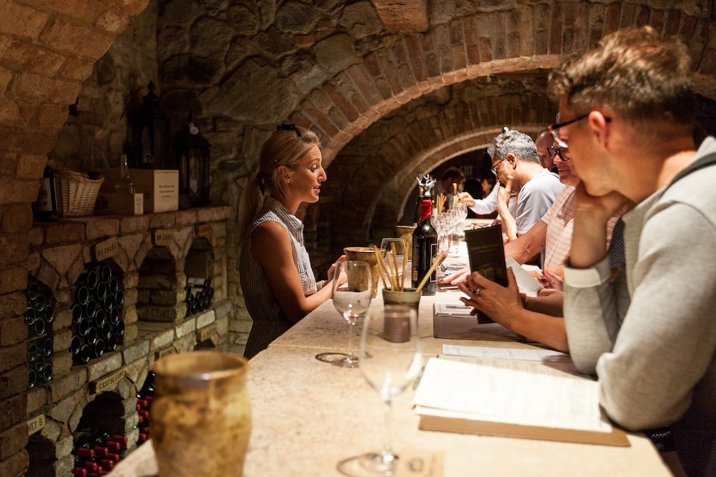 Visitors sit at a bar in a wine cellar, tasting wine.