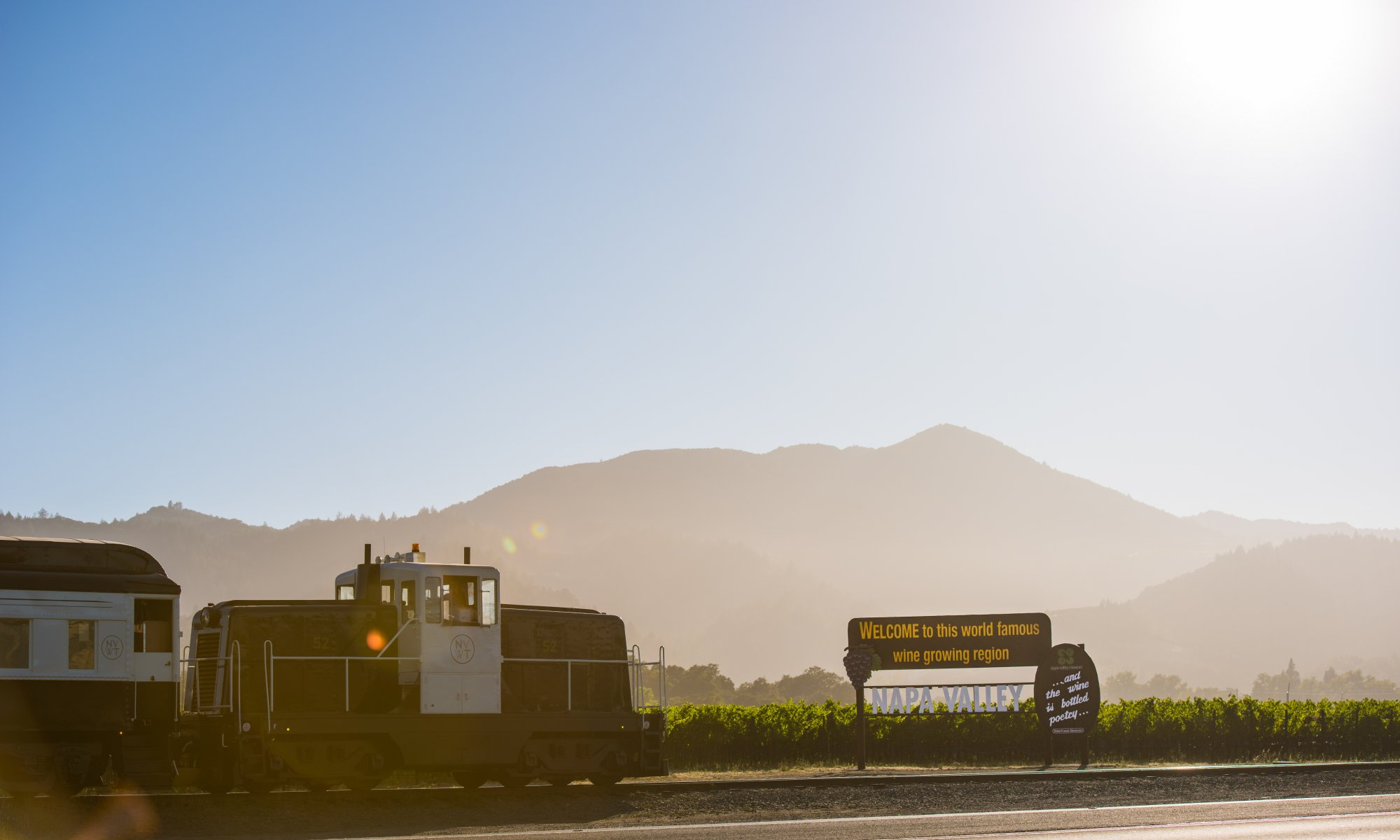 The Napa Valley Wine Train engine next to a Welcome to Napa sign with mountains in background