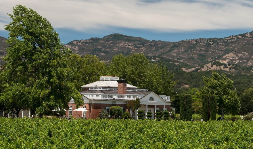 Large white and brick building in lush green vineyard with mountains in background