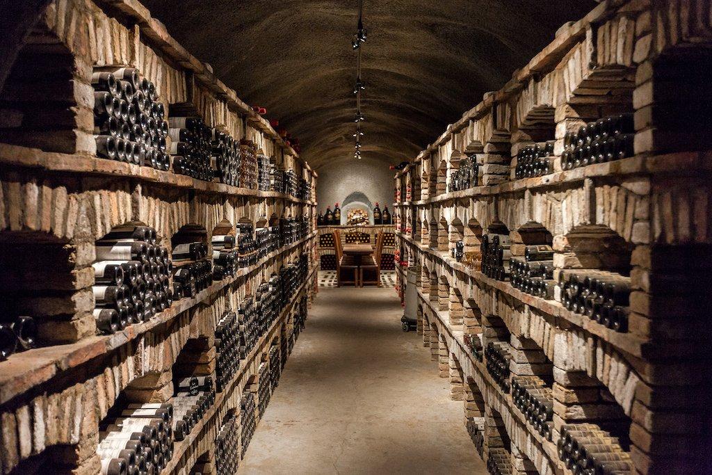 An underground wine cellar filled with wine.