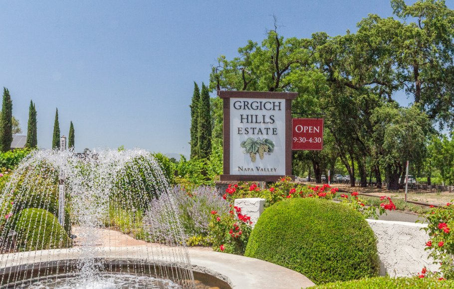 The entrance to Grgich Hills Estate Winery on a sunny day with water fountain and green trees surrounding