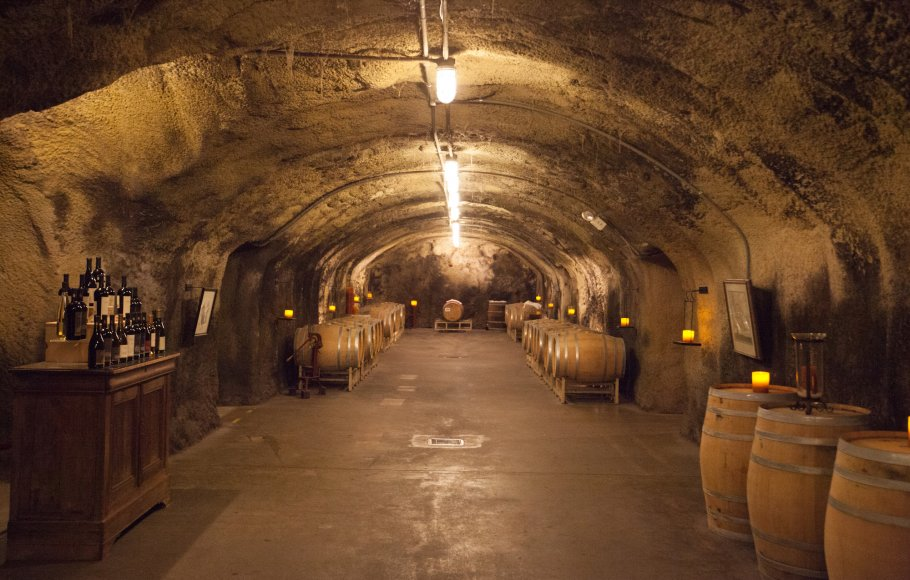 An underground wine cellar in Napa Valley lined with wooden barrels, and table of wine bottles to the left