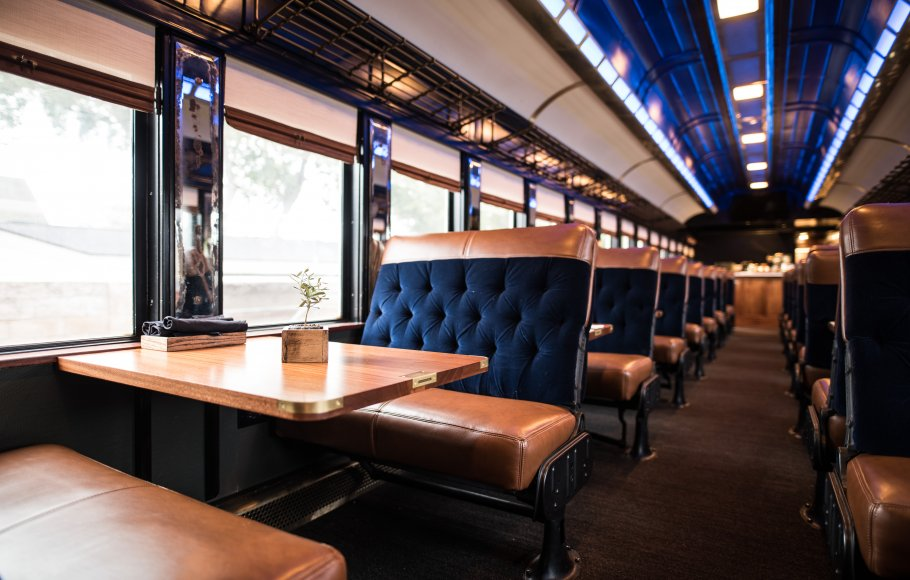 Blue velvet lounge seats and mahogany tables in a dining railcar on Napa Valley Wine Train