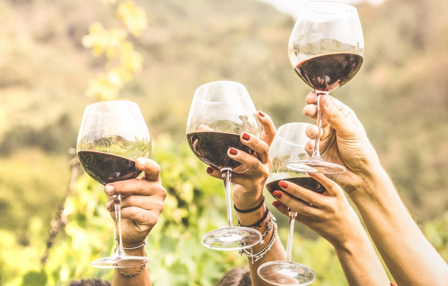Up close of 4 hands holding glasses of red wine in the air in Napa Valley