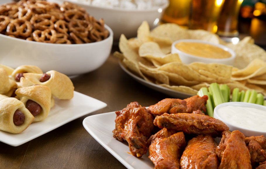 Party snacks: Hot wings, pig in the blankets, pretzels, nacho chips and popcorn displayed on white plates on a dark wood table