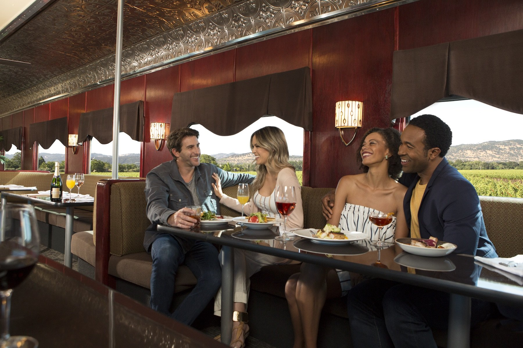 Two couples enjoying wine and a meal aboard the Napa Valley Wine Train.