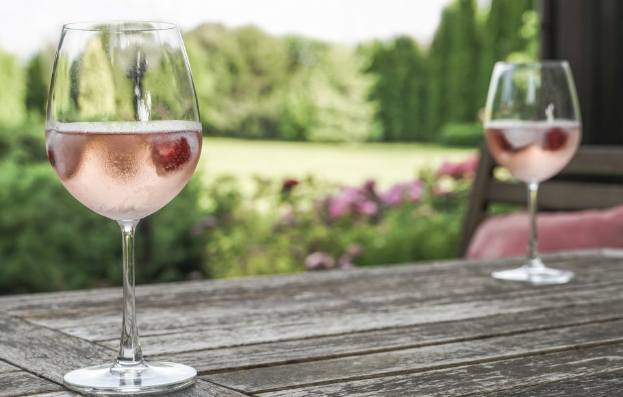 rose wine glasses on a wooden table at garden