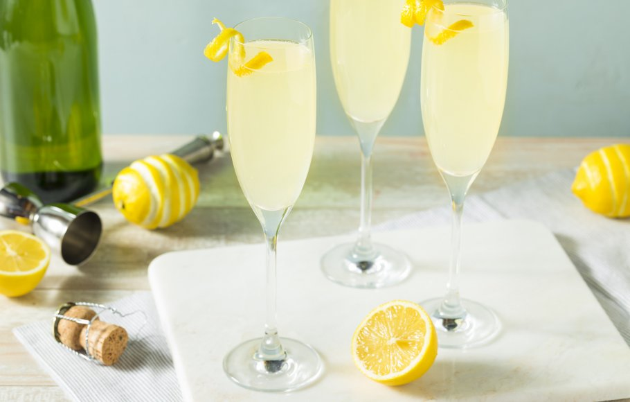 Three champagne flutes with French 75 cocktails, lemons, and a champagne cork.