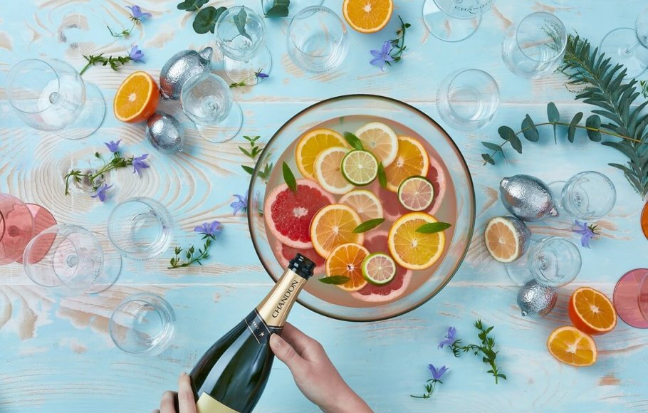 Overhead view of a large bowl of citrus sangria and someone pouring Chandon sparkling wine