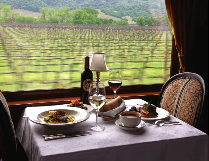 2 glasses of wine and 2 plates of food on a table on the Napa Valley Wine Train
